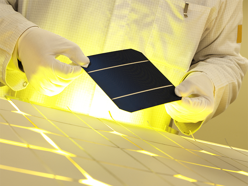 a tech worker holds a piece of a solar panel