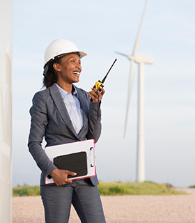 Image of woman using a walkie-talkie in front of a windmill.