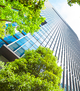Image of office building with green trees in front.