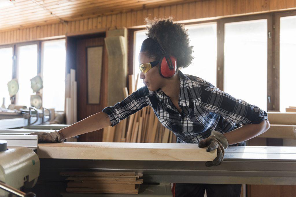 Carpenter pushing a block of wood through a table saw.