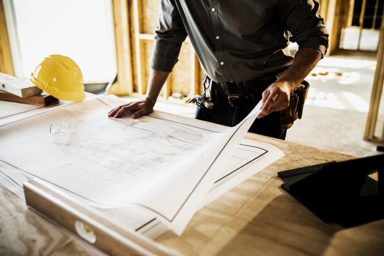 Builder reviewing blueprints.