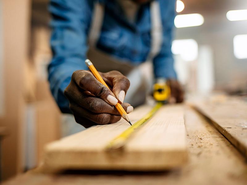 A carpenter measures a board.