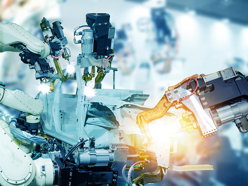 Robotic arms weld a piece of metal.