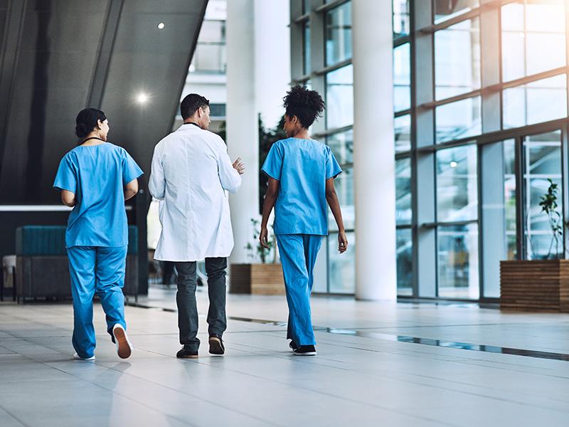 Doctors walk down a hospital corridor.